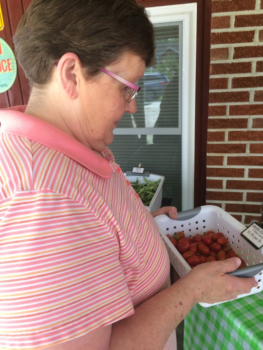 Debbie Goosie from Norwood takes a container of cherry tomatoes to the counter area.