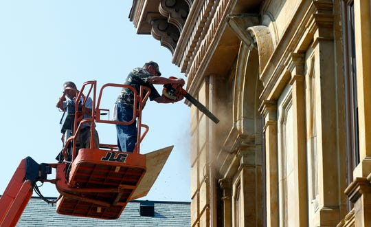 Henry Brothers General Contractors workers clear debris off a ledge of the old Fairfield County Courthouse Tuesday morning, Aug. 20, 2019, in downtown Lancaster. Contractors were repairing soffits on the building, which houses county administrative offices.