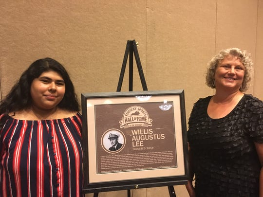Annie Juarez, left, and Denise Humphries flank the plaque honoring Admiral Willis Lee, the five-time Olympic gold medalist whose cause they championed for the Kentucky Sports Hall of Fame. Monday, Aug. 19, 2019