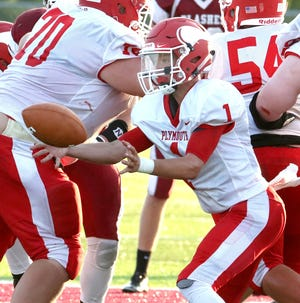 Plymouth QB Walker Elliot pitches the ball back to his running back during a game at Willard last season. Elliott is expected to be a top returner for the Big Red in 2019.