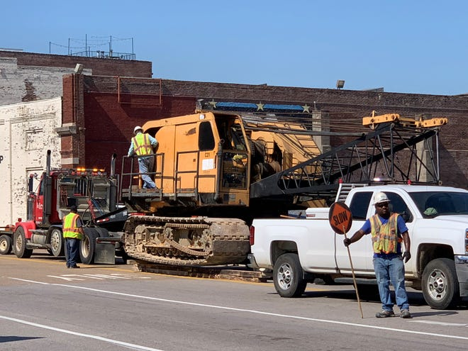 Construction crew stand outside of the site for the One Beale Street project August 20, 2019. One man directs traffic flow.