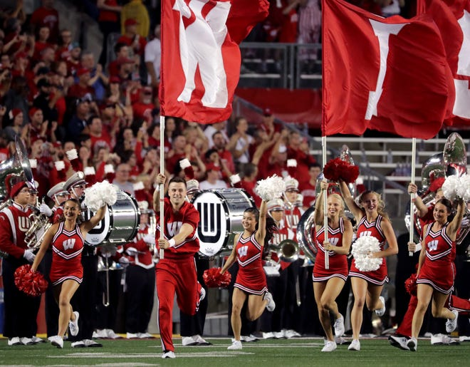 Wisconsin cheerleaders lead the football team onto the filed before their game against Western Kentucky on Aug. 31, 2018 at Camp Randall Stadium in Madison.
