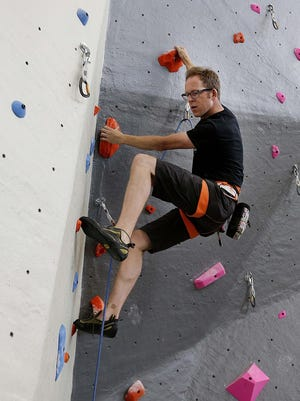 Craig Burzynski, co-owner of Adventure Rock, scales the indoor rock-climbing wall at Adventure Rock's Riverwest facility in 2016. Adventure Rock plans to open another center in Walker's Point.