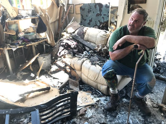 Gassville Garden Apartments resident David Orin sits in the ruins of his living Tuesday after fire ripped through several apartments at the complex, injuring one resident. Orin was in his apartment with Gassville Fire Chief Michael Glotzl who was salvaging items for Orin.