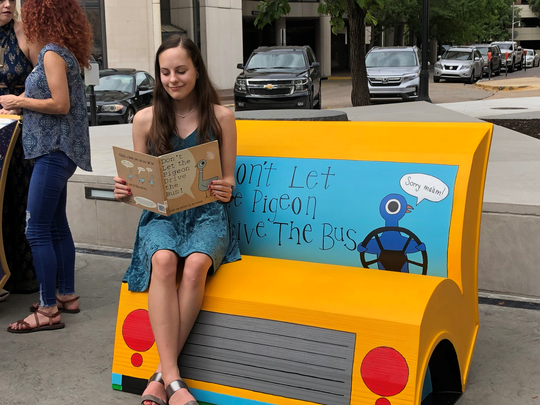 Zoe Barker sitting on the book bench the city commissioned her to complete. Barker's literary-themed bench will be installed at E.L. Lowder Bench Library.