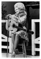 Dolly Parton seated on set of the Porter Wagoner Show.