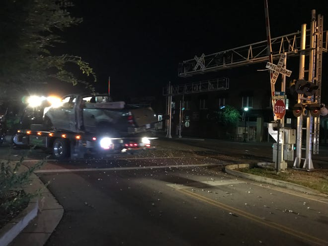 A truck hit by a train is towed off early Wednesday morning.