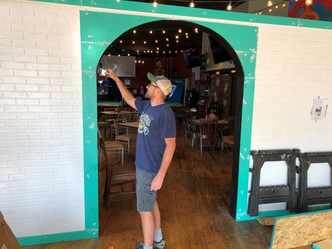 Spencer Wakefield paints a new wall separating Filly's from what will soon be a new ice cream shop called The Ice Cream Social.