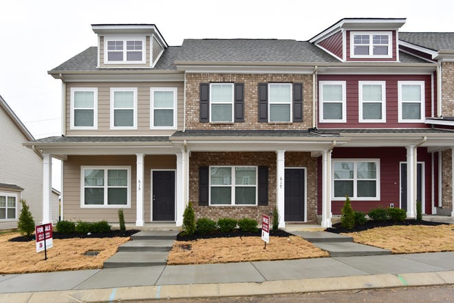 Townhome exteriors at Bradburn Village, a neighborhood of 132 residences at the intersection of Murfreesboro Road and Pinhook Road. A Publix grocery store is next door.