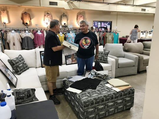Jim Reid, left, shows a customer some of the fabric choices in his furniture booths at the Nashville Flea Market.