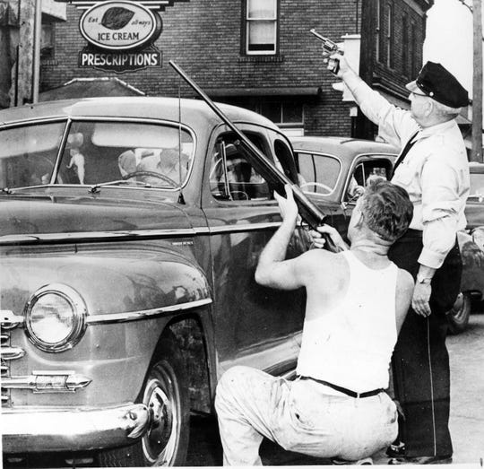Police officers point their guns at Howard Unruh's apartment during a standoff in Camden on Sept. 6, 1949. Unruh's shooting rampage left 13 people dead, including 3 children, and several others injured.