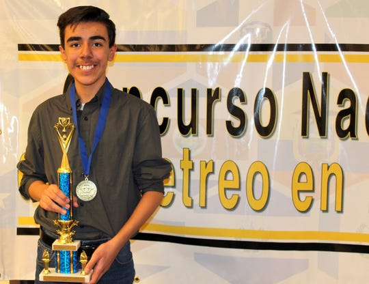 Maximiliano Hultsch Martinez, 14, holds his national championship trophy from the National Spanish Spelling Bee.