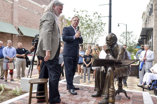 Randy Bowden, left, and Quint Studer stand at the foot of the new J. Earle Bowden statue as it's unveiled at Southtowne on Tuesday, Aug. 20, 2019.