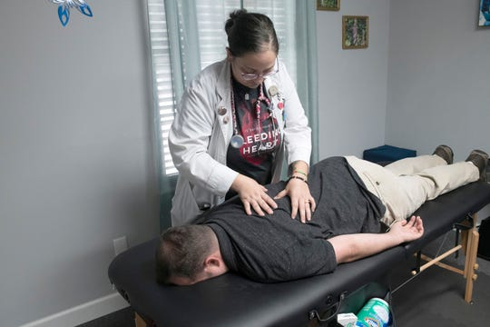 Dr. Alexys Hillman demonstrates an acupressure technique on her husband and office manager on Tuesday.
