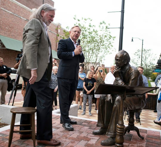 Randy Bowden, the son of late Pensacola News Journal Editor Emeritus J. Earle Bowden, looks at his father's statue as Quint Studer unveils the new J. Earle Bowden Plaza at Southtowne on Tuesday.