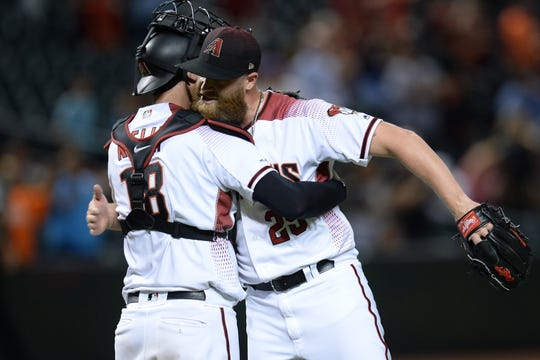 Diamondbacks reliever Archie Bradley hugs catcher Carson Kelly after the ninth inning of a victory over the Rockies on Aug. 19 Chase Field.