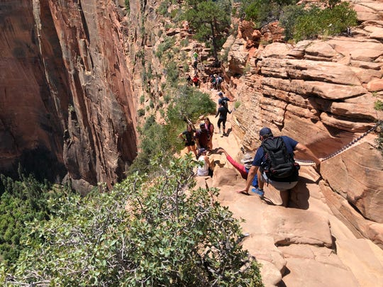 Hikers use chains to traverse the top of the Angels Landing trail in Zion National Park. People have died falling from this trail. Be kind to fellow hikers by taking turns on this dangerous stretch.