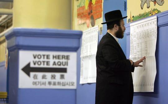 Un hombre judío busca su casilla de votación en New York.