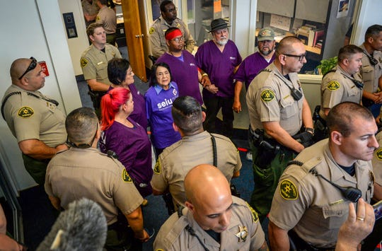 Labor leader Dolores Huerta, center, joins several other protesters in linking arms outside the Fresno County Board of Supervisors chambers shortly before being arrested Tuesday, Aug. 20, 2019, in Fresno, Calif. Huerta has been arrested along with several other union members during a protest to demand a raise for Fresno county home care workers. The Fresno Bee reports sheriff deputies put Huerta and the others in plastic handcuffs and removed them Tuesday from the entrance to the Board of Supervisors chambers, where supervisors were holding a closed meeting. (Craig Kohlruss/The Fresno Bee via AP)
