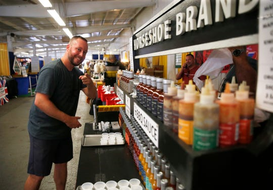 Ryan Fleischhauer of Horseshoe Brand hot sauce prepares their booth in the specialty foods pavilion at the 2019 Dutchess County Fair in Rhinebeck on August 20, 2019.