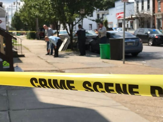 York City Police detectives look at evidence following a shooting in the 200 block of East Philadelphia Street on Tuesday afternoon.