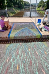 Carol Oldenburg, first place winner, takes a break while painting her Street 2 Creek Storm Drain Art Project on the Market Street bridge over the Codorus Creek in York. The project is designed to remind the public of the negative impacts of what goes down storm drains.