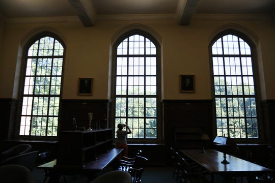 Marina Beck takes photos of the tress that line the view out the windows of the historic library in the Colgate Rochester Crozer Divinity School in this August 2019 file photo.