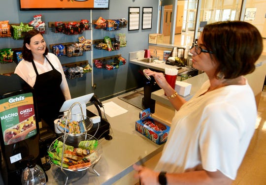 Bossier Parish high school student Leslie Nelson listens to assistant principle, Amy Washington, as she gives instructions on how to run the cafe at the Bossier Parish School for Technology and Innovative Learning center.