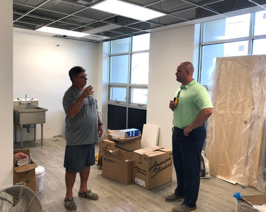 Standing in the new athletic training room, Waynesboro High School athletic director Derek McDaniel (left) and principal Bryan Stamm discuss the ongoing renovations at the school.