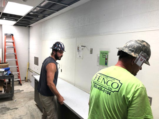 Construction workers place a counter top in the Waynesboro High School concession stand.