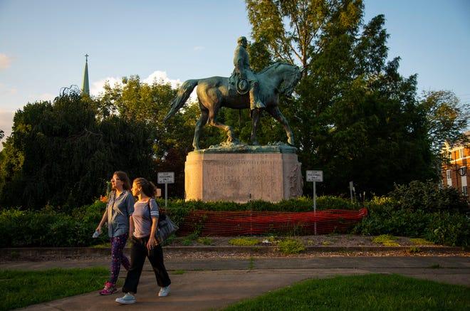 Women walk past the statue of Robert E. Lee in Market Street Park.