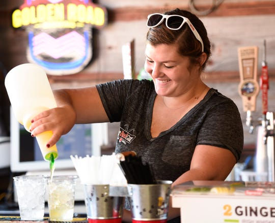 Ashley Anderson pours drinks at the outdoor bar Friday, Aug. 16, 2019, at The Red Goat Bar & Grill in Watkins.