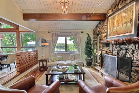 Shiplap and exposed beam ceilings hover over the living room which has at its center a stone fireplace and impressive hearth.