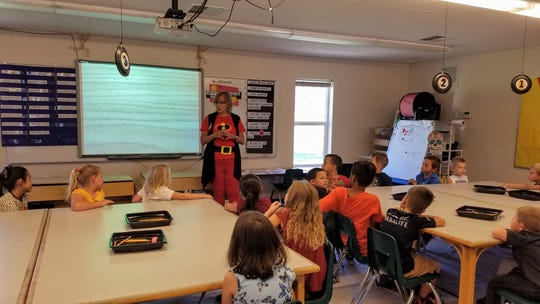 "Kelly McDonald, the art specialist at Red Mountain Elementary School in Ivins, dons a ""The Incredibles"" costume as she works with second graders during an art class on Friday, Aug. 17, 2019."