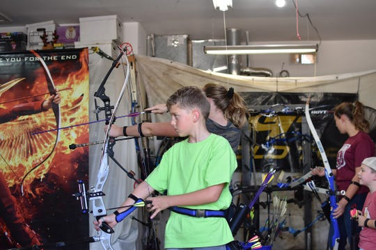 Nixon Treanor goes through the steps of firing his bow during archery lessons.