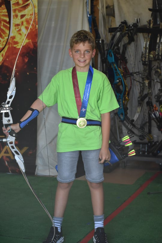 Nixon Treanor shows off his gold medal from the Utah State Archery Outdoor Championships in July, 2019.