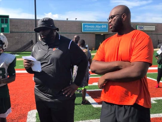 FAMU right tackle Calvin Ashley observes practice with position coach Alex Jackson.