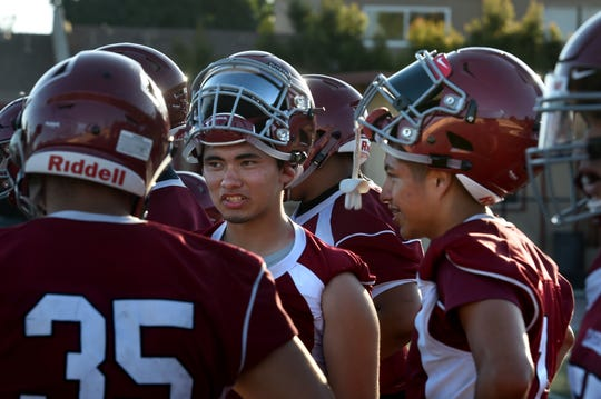 Santa Paula High quarterback Hector Zuniga, center, and wide receiver Victor Duran, right, talk between plays during Monday's practice.