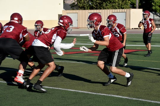 Santa Paula High's Johnny Govea (right) gets ready to engage a teammate during Monday's practice. Govea is one of the top returning defensive lineman for the Cardinals.