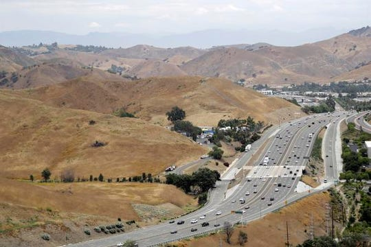 Highway 101 passes between two open space preserves on conservancy lands in the Santa Monica Mountains in Agoura Hills, Calif., in this July 25, 2019, photo.  Hoping to fend off the extinction of mountain lions and other species that require room to roam, transportation officials and conservationists will build a mostly privately funded wildlife crossing over this freeway. It will give big cats, coyotes, deer, lizards, snakes and other creatures a safe route to open space and better access to food and potential mates. (AP Photo/Marcio Jose Sanchez)