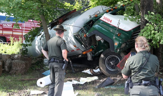 New York State Environmental Police look over the tanker truck that crashed off Peekskill Hollow Road at the bottom of Tinker Hill Road Aug. 19, 2019. The driver was injured and the truck leaked a large amount of it's contents which is used for asphalt work.