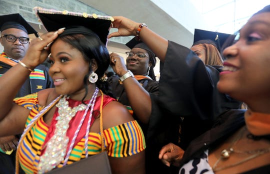 Nancy Sarpong gets help with her cap before the College of New Rochelle's final graduation ceremony Aug. 20, 2019. The 115 year old college, which is closing as the summer semester comes to an end, held the graduation ceremony for students who completed their degree requirements over the summer.