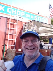 UD Professor Dave Redlawsk shows off a pork chop on the stick at the Iowa State Fair.
