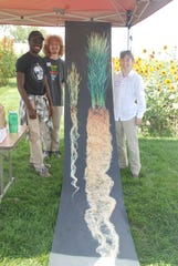 Three researchers, left to right, Korede Olugbenle, Joel Cryer and Stephania Cartoni explained the virtues of a deep-rooted perennial intermediate wheatgrass variety that is being trialed at various agricultural research stations in Wisconsin for its value in forage and grain production. Their to-scale poster shows the depth of roots the plant sends down.