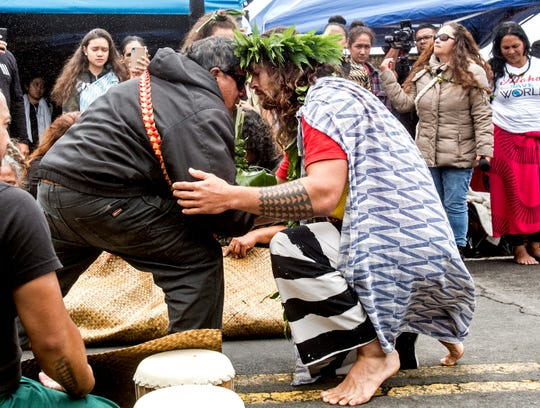Actor Jason Momoa exchanges a traditional greeting with an elder while visiting elders and Native Hawaiian protesters blocking the construction of a giant telescope on Hawaii's tallest mountain, at Mauna Kea Access Road on Wednesday, July 31, 2019, in Mauna Kea, Hawaii.