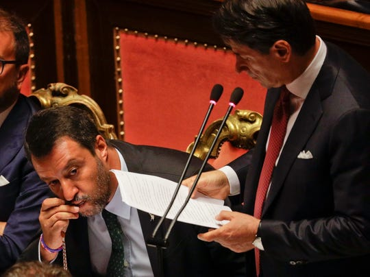 Italian Premier Giuseppe Conte addresses the Senate as Deputy-Premier Matteo Salvini kisses a rosary while sitting beside him, in Rome, Tuesday, Aug. 20, 2019.