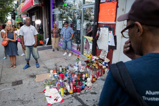 Pedestrians stand beside a memorial for Eric Garner on July 22, 2014 in New York.