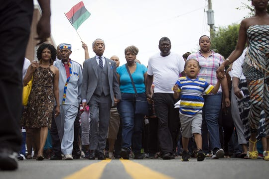 Rev. Al Sharpton and members of Eric Garners family march towards the site of his death following a service held in his name at the Mount Sinai Center for Community Enrichment on July 19, 2014.