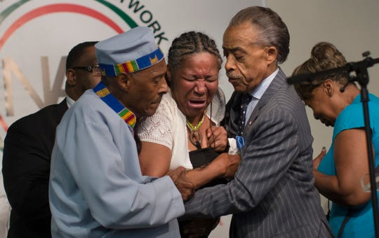 Esaw Garner, wife of Eric Garner, breaks down in the arms of Rev. Herbert Daughtry, center, and Rev. Al Sharpton, right, during a rally at the National Action Network headquarters for Eric Garner on July 19, 2014, in New York.