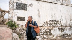 Wanda Tucker sits outside of the Fortaleza de Massangano on Saturday, Aug. 3, 2019 in Angola. The fort would have been the first place Africans were captured, branded and baptized before walking or being transferred by canoe down the Kwanza river to Angola for transport via the Transatlantic slave trade.